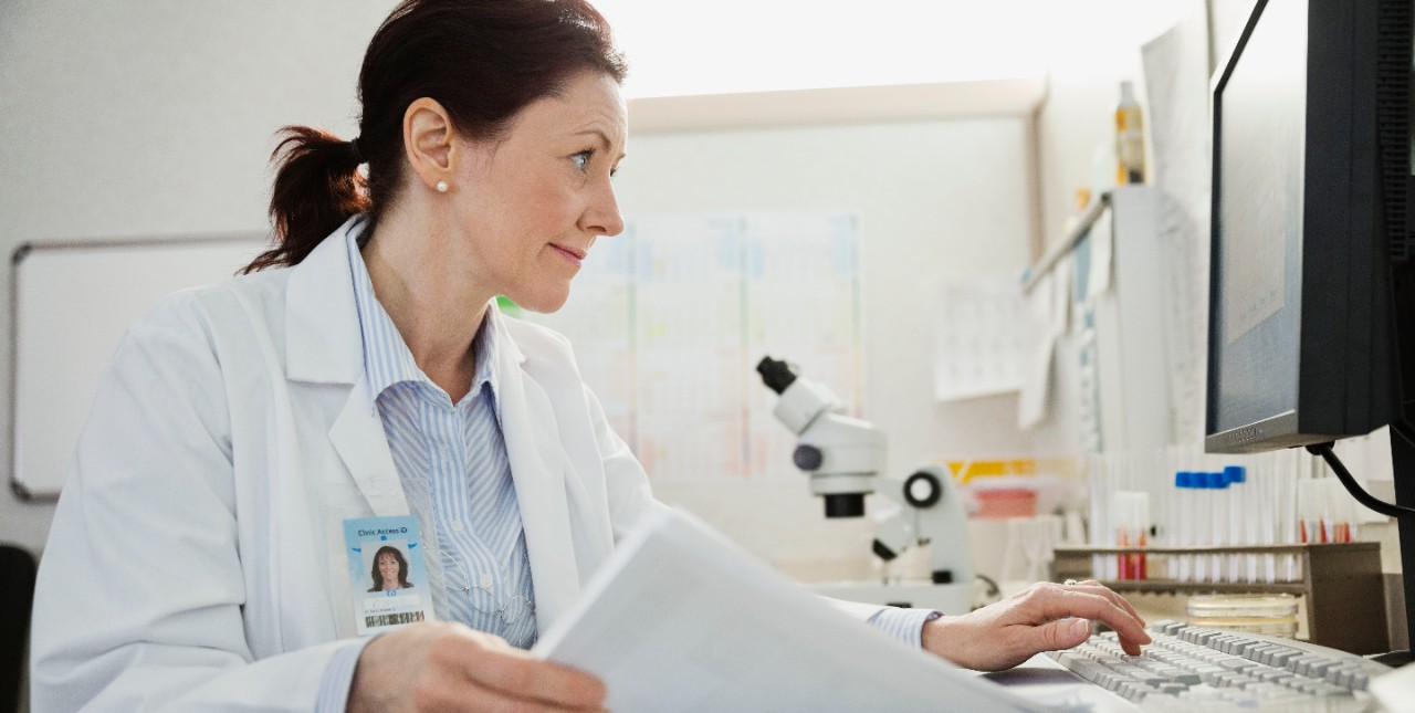 Doctor using computer while reviewing records at desk in clinic, individual, woman