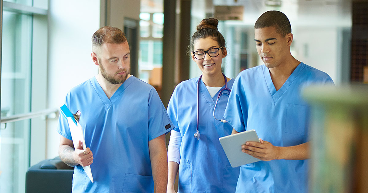 Three doctors walking along a hospital corridor discussing case and wearing scrubs, group, walk