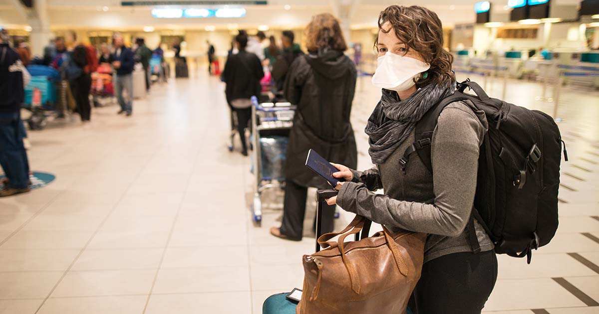 1215339540 Woman waiting in a long line for a flight wearing a N95 face mask during a global pandemic